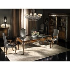 Fine carvings and a etched glass top highlight this dining set.